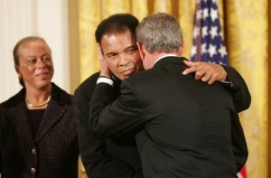 As Mrs. Lonnie Ali looks on, President George W. Bush embraces three-time heavyweight boxing champion of the world Muhammad Ali after presenting him with the Presidential Medal of Freedom Wednesday, Nov. 9, 2005, during ceremonies at the White House. White House photo by Paul Morse, courtesy of the George W. Bush Presidential Library and Museum/NARA.