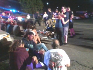 """Victims are tended to in the parking lot of an Aurora theater, where a mass shooting occurred during the premiere of """"The Dark Night Rises,"""" July 20, 2012."""