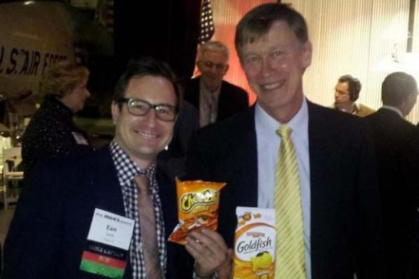 "Gov. John Hickenlooper, right, poses with Ean Seeb, co-owner of Denver Relief, one of the state's largest dispensaries, holding Cheetos and Goldfish, the two things Hickenlooper told marijuana users not to ""bust out"" too quickly in the wake of Amendment 64's passage. (Photo: Denver Relief Consulting)"