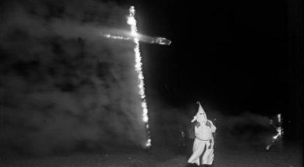 A Ku Klux Klan member burns a cross on Ruby Hill in Denver. (Credit: Wikimedia Commons)