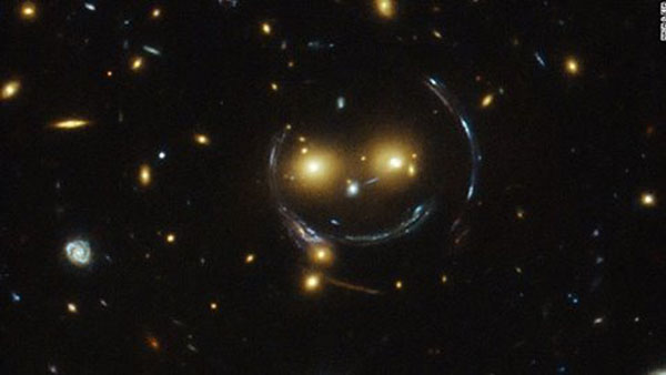 A massive galaxy cluster known as SDSS J1038+4849 looks like a smiley face in an image captured by the Hubble Space Telescope.