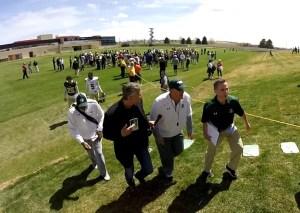 FOX31 Denver's Chris Halsne, black coat/center, confronts Colorado State coach Mike Bobo.