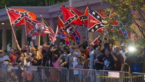 People wave Confederate flags as President Barack Obama arrives at his hotel in Oklahoma City on Wednesday, July 15, 2015. (Photo: SAUL LOEB/AFP/Getty Images)