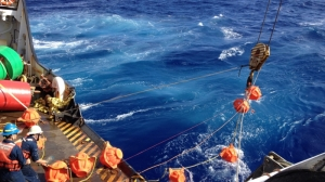Hauling up hydrophone during the Challenger Deep mission in 2015. (NOAA)