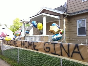 A banner and balloons decorated a fence to welcome Gina DeJesus home.
