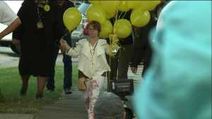 (Michelle Knight hands out balloons on Seymour Avenue.)