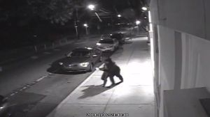 A man is seen on surveillance video grabbing and dragging a woman into a car in Philadelphia Sunday night. Courtesy: Philadelphia Police