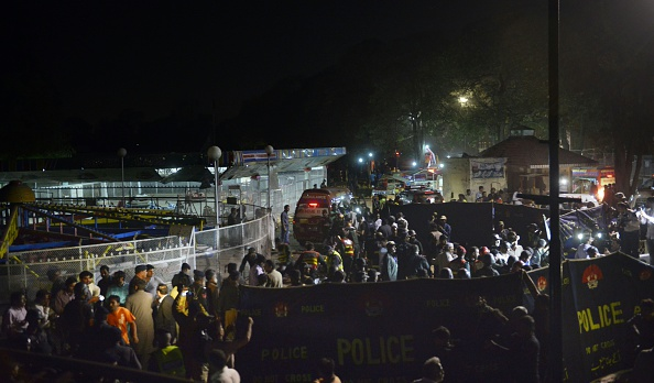 Pakistani rescuers and officials gather at a bomb blast site in Lahore on March 27, 2016. At least 25 people were killed and dozens injured when an explosion ripped through the parking lot of a crowded park where many minority Christians had gone to celebrate Easter Sunday in the Pakistani city Lahore, officials said. / AFP / ARIF ALI (Photo credit should read ARIF ALI/AFP/Getty Images)