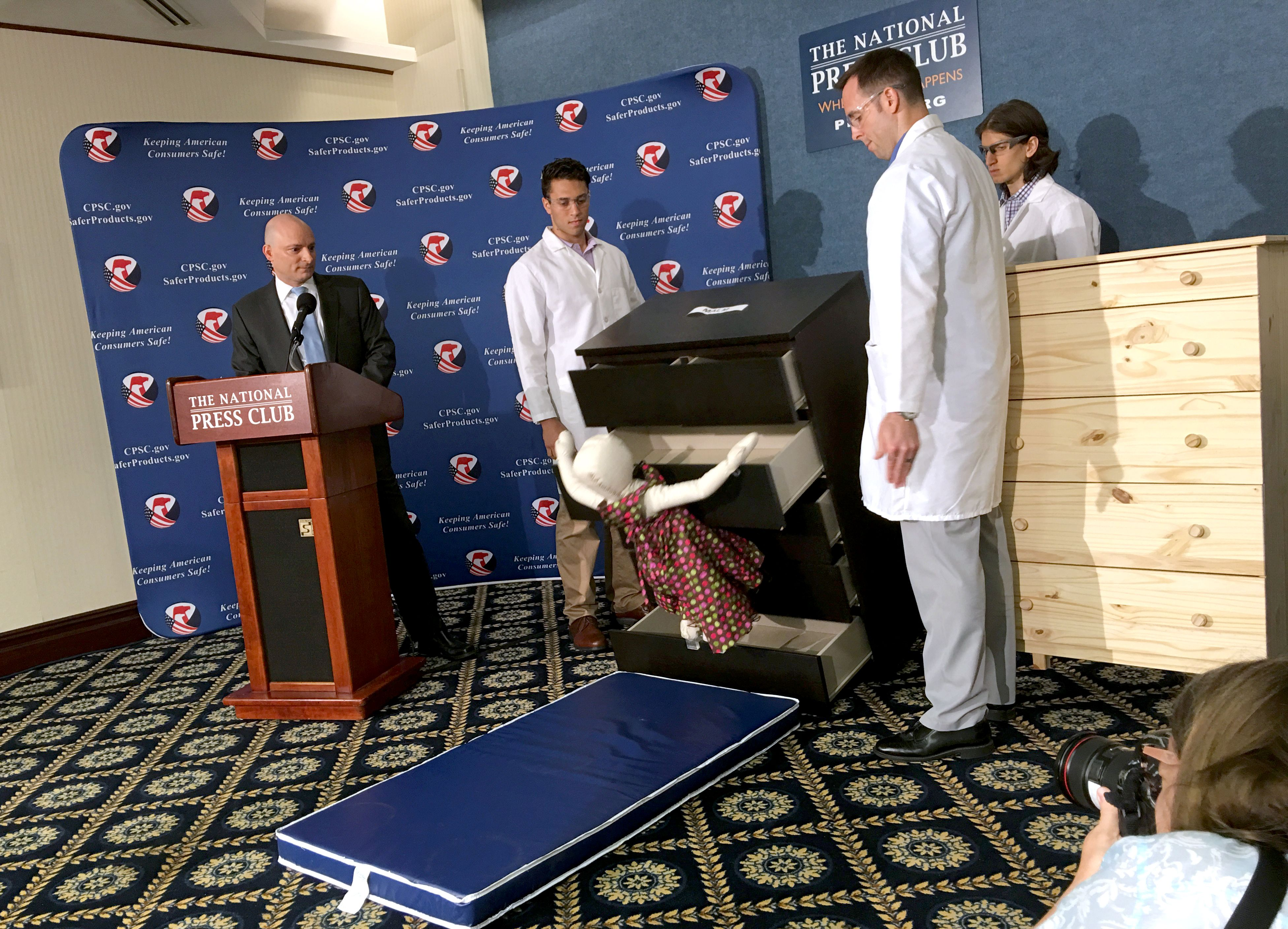 Elliot Kaye (L), chair of the Consumer Product Safety Commission (CPSC) and CPSC employees watch as a 28-pound (13 kilo) dummy(C) falls over and under IKEAs Malm model chest of drawers, during a live demonstration at the National Press Club in Washington, DC 28 June, 2016. (AFP / Carlos Hamann)
