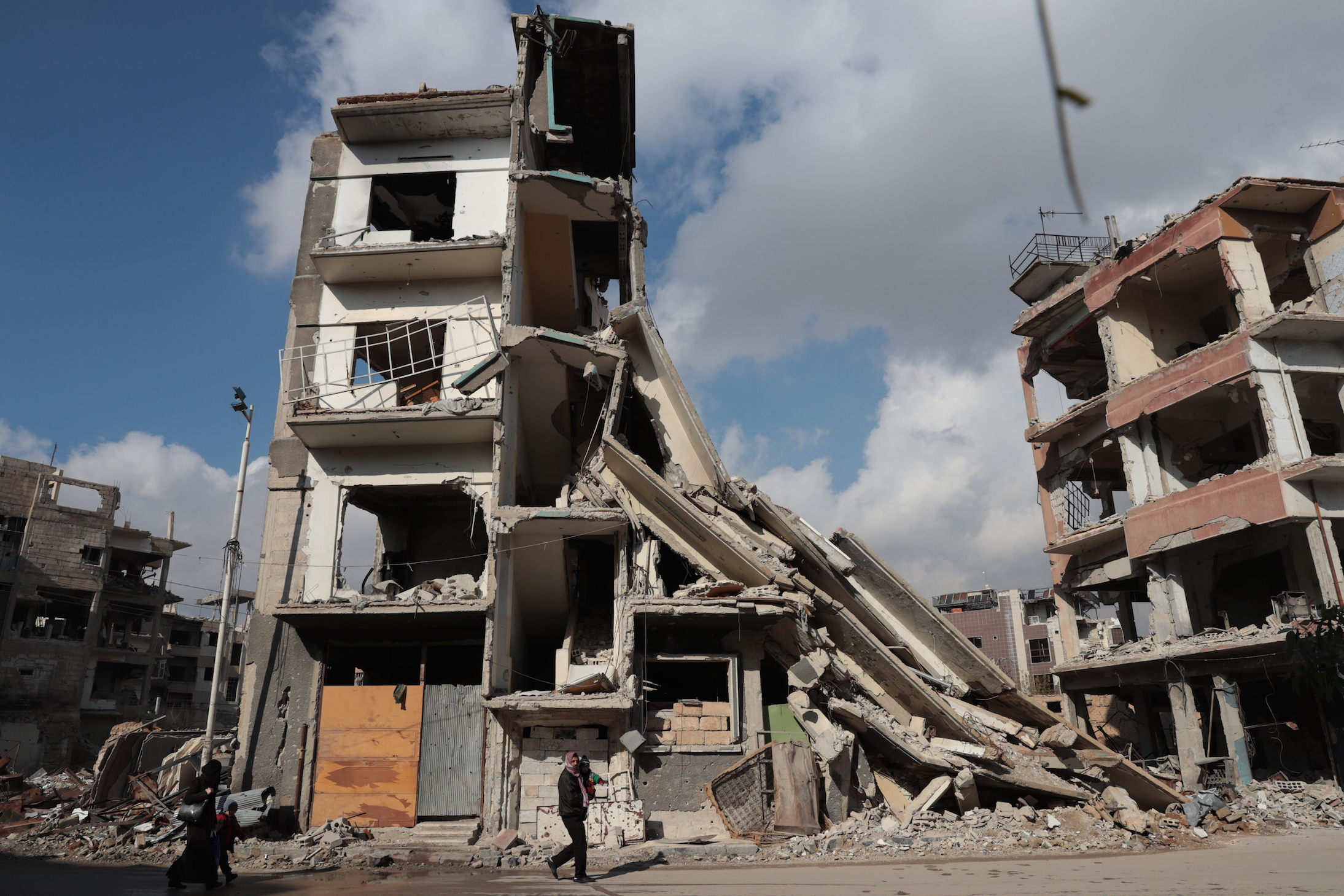 Syrians walk past a destroyed building in the rebel-held town of Douma, on the eastern outskirts of Damascus, on December 30, 2016, on the first day of a nationwide truce. Clashes erupted between Syrian government forces and opposition fighters in an area outside Damascus, despite a nationwide truce that began at midnight, a monitor said. / AFP / Abd Doumany        (Photo credit should read ABD DOUMANY/AFP/Getty Images)
