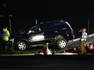 The car that hit the billboard is loaded onto a tow truck.