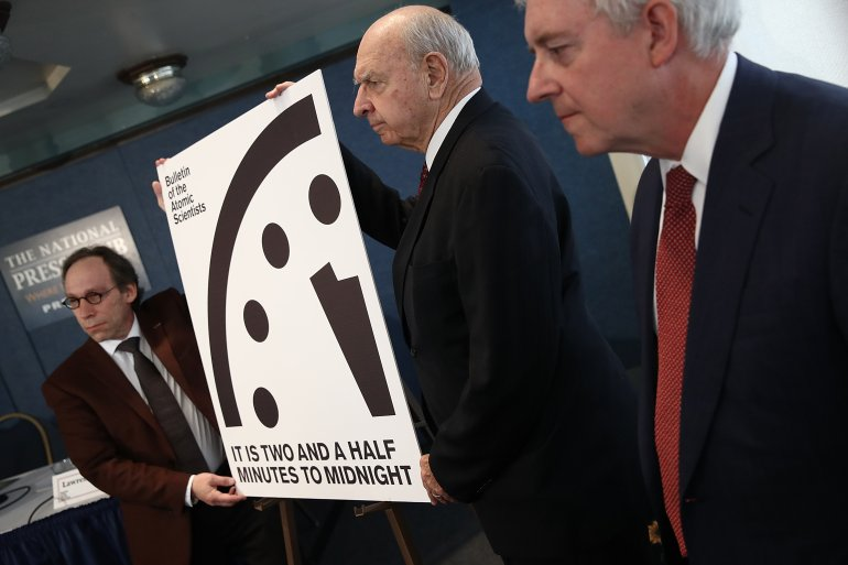 """Members of the Bulletin of Atomic Scientists unveil the 2017 time for the """"Doomsday Clock"""" January 26, 2017 in Washington, DC. For the first time in the 70-year history of the Doomsday Clock, the Bulletin of Atomic Scientists moved the clock forward 30 seconds to two and a half minutes before midnight, citing """"ill-considered"""" statements by U.S. President Donald Trump on nuclear weapons and climate change, developments in Russia, North Korea, India and Pakistan. From left to right are theoretical physicist Lawrence Krauss, former U.S. Ambassador to the United Nations Thomas Pickering and retired U.S. Navy Rear Admiral David Titley.  (Photo by Win McNamee/Getty Images)"""