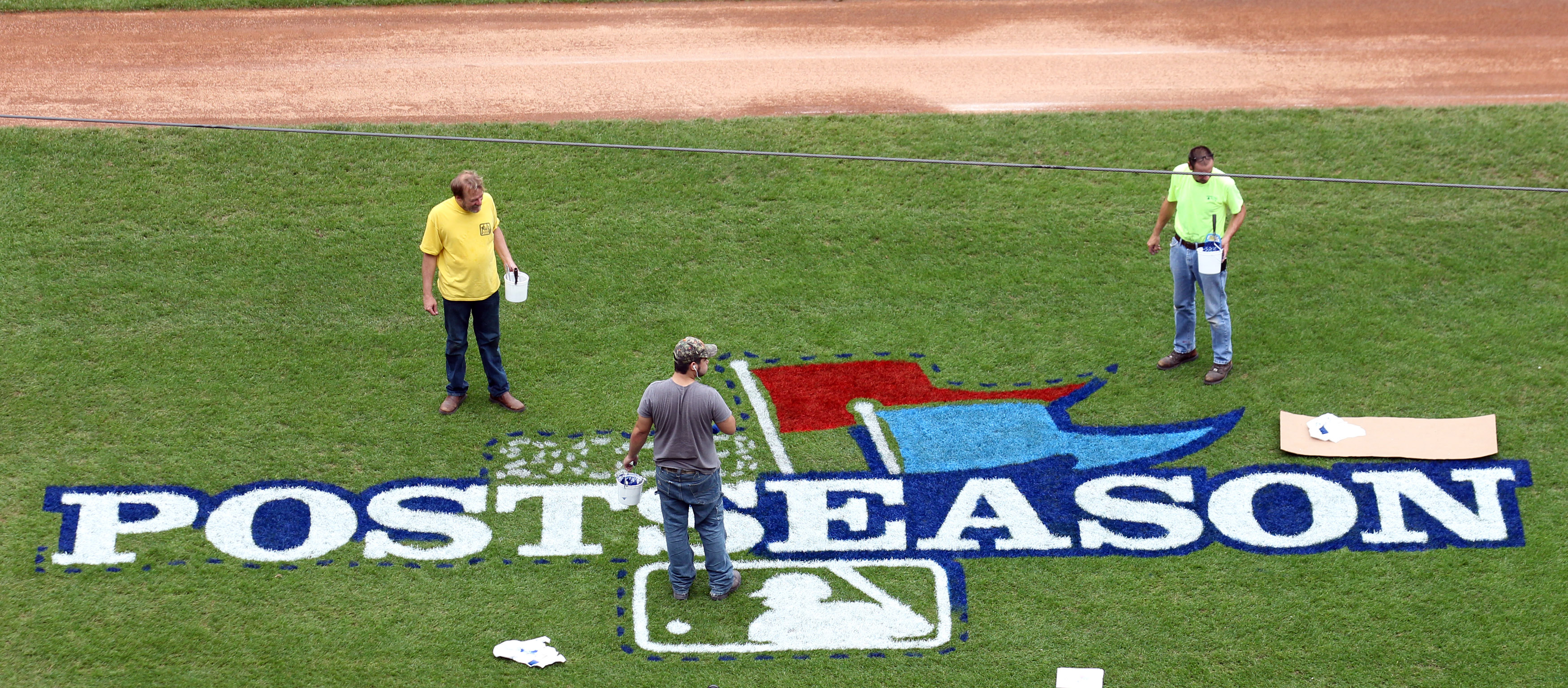 Painters from Warren Sign Company stop to check their progress as they paint a postseason logo on the field at Busch Stadium in St. Louis on October 1, 2013. The St. Louis Cardinals will face the winner of the Cincinnati Reds-Pittsburgh Pirates game on October 4, 2013 for game one.   UPI/Bill Greenblatt