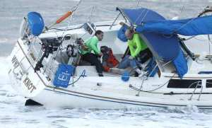 A man is pulled from the cabin of a sailboat that ran aground in Laguna Beach. (Credit: Don Leach / Coastline Pilot)