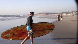 Drew Brees carries his stand up paddle surfboard in Del Mar.