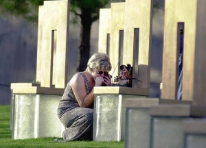 Renee Pendley listens to news of Timothy McVeigh's execution with a portable TV as she crouches next to a chair representing her slain friend Teressa Lauderdale in the Field of Empty Chairs sector of the Oklahoma City National Memorial in downtown Oklahoma City 11 June 2001. (Getty Images)