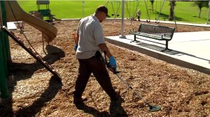 A park worker searches for razor blades at Harvest Park in Chula Vista