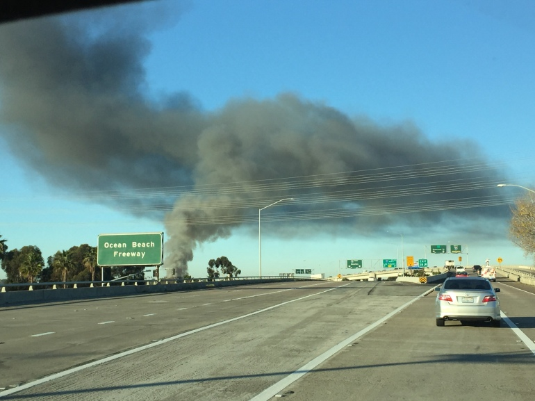Plume of smoke in Midway District was seen for miles around.