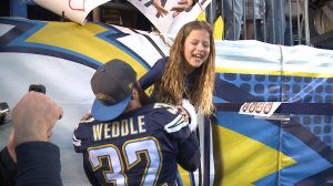 Eric Weddle helps his daughter down to the field at Qualcomm Stadium during the Chargers last home game of the 2015 season.