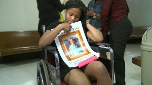 A 12-year-old girl holds a picture of another girl who was brain dead after the two them were hit by a car.