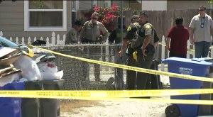 Investigators tape off road near AutoZone to investigate a shooting.