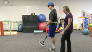Giancarlo Gil is learning to walk again with help from therapist April Coyle.