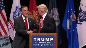 Darrell Issa and Donald Trump shake hands during a political rally.