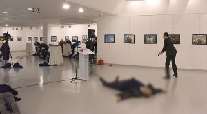 This picture taken on December 19, 2016 shows Andrey Karlov (2ndR), the Russian ambassador to Ankara, lying on the floor after being shot by a gunman (R) during an attack during a public event in Ankara. (STRINGER/AFP/Getty Images)