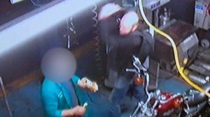 The violent attack was captured on one of the auto shop's security cameras.