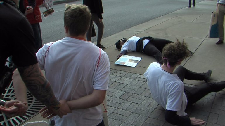 """Demonstrators stage a """"die-in"""" on the sidewalk of the Country Club Plaza."""