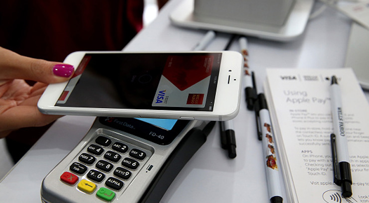 SAN FRANCISCO, CA - OCTOBER 20:  A worker demonstrates Apple Pay inside a mobile kiosk sponsored by Visa and Wells Fargo to demonstrate the new Apple Pay mobile payment system on October 20, 2014 in San Francisco City. Apple's Apple Pay mobile payment system launched today at select banks and retail outlets.  (Photo by Justin Sullivan/Getty Images)