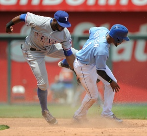 KANSAS CITY, MO - JUNE 6:  Jarrod Dyson #1 of the Kansas City Royals slides into second for a steal past Hanser Alberto #68 of the Texas Rangers in the third inning at Kauffman Stadium on June 6, 2015 in Kansas City, Missouri. (Photo by Ed Zurga/Getty Images)