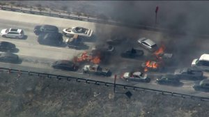 Cars are seen burning from a fast-moving wildfire along I-15 outside of Los Angeles on Friday. (Credit: KTLA)