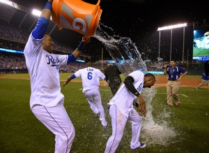 Jarrod Dyson #1 and Lorenzo Cain #6 of the Kansas City Royals are doused with water by Salvador Perez #13 of the  after a 3-2 win over the Minnesota Twins in ten innings at Kauffman Stadium on July 3, 2015 in Kansas City, Missouri. (Photo by Ed Zurga/Getty Images)