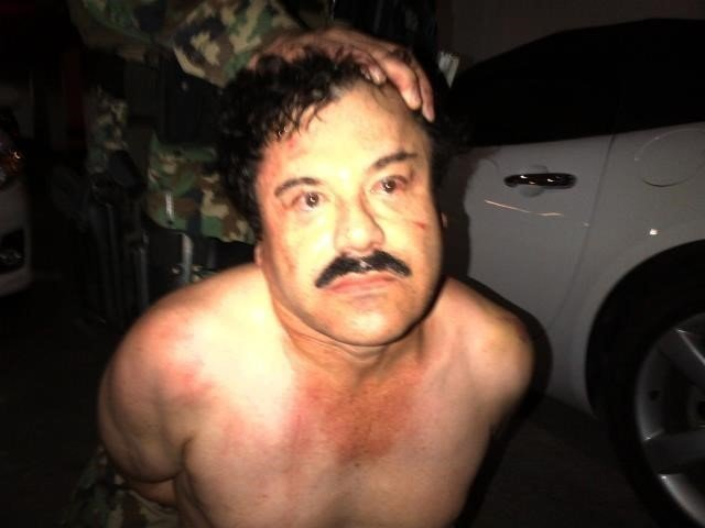 """Photo: El Chapo under arrest (2014) A manhunt has been launched to find Mexican drug kingpin Joaquin Guzman after he escaped from prison, Mexico's National Security Commission said in a statement Saturday. Guards at the Altiplano Federal Prison found that Guzman, also known as """"El Chapo,"""" was missing during routine check."""