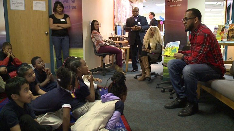 """Chiefs linebacker Derrick Johnson reads to students as part of his """"Defend the Dream"""" foundation."""