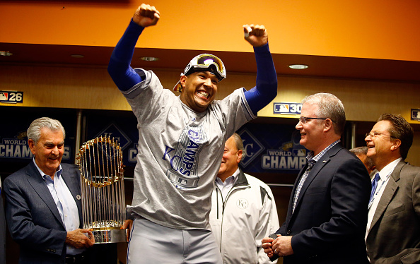 NEW YORK, NY - NOVEMBER 01: Salvador Perez #13 of the Kansas City Royals celebrates in the clubhouse as Kansas City Royals owner David D. Glass (L) holds the Commissioner's Trophy after the Kansas City Royals defeat the New York Mets to win Game Five of the 2015 World Series at Citi Field on November 1, 2015 in the Flushing neighborhood of the Queens borough of New York City. The Kansas City Royals defeated the New York Mets with a score of 7 to 2 to win the World Series. (Photo by Al Bello/Getty Images)
