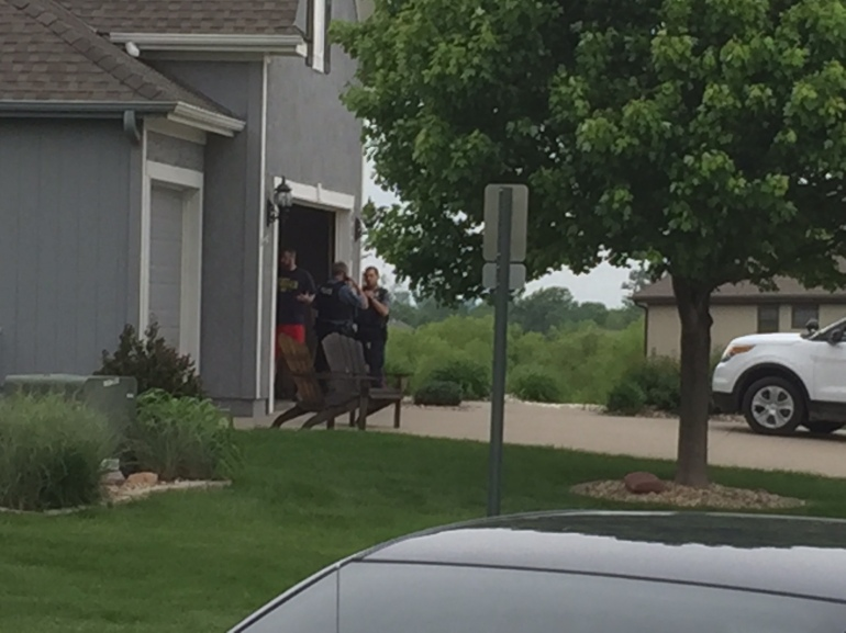 Multiple KCK detectives at a home in Basehor, Kan., Monday afternoon. Police reportedly found a vehicle that was possibly taken by the suspect in the detective's shooting. Basehor is approximately nine miles west of Kansas Speedway.