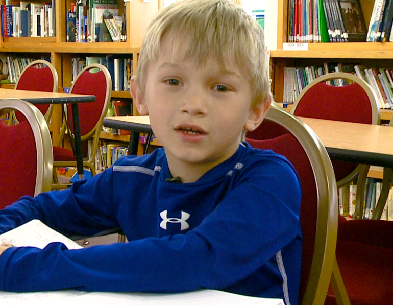 J.W., 7, brought in money and wore blue for the Lancaster family.