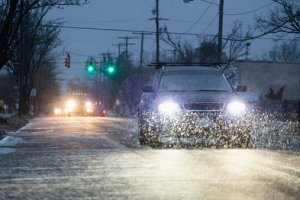 Car driving on snowy urban street at night Spaces Images