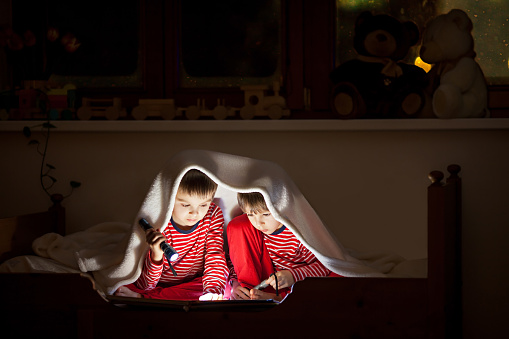 Two sweet boys, reading a book in bed after bedtime