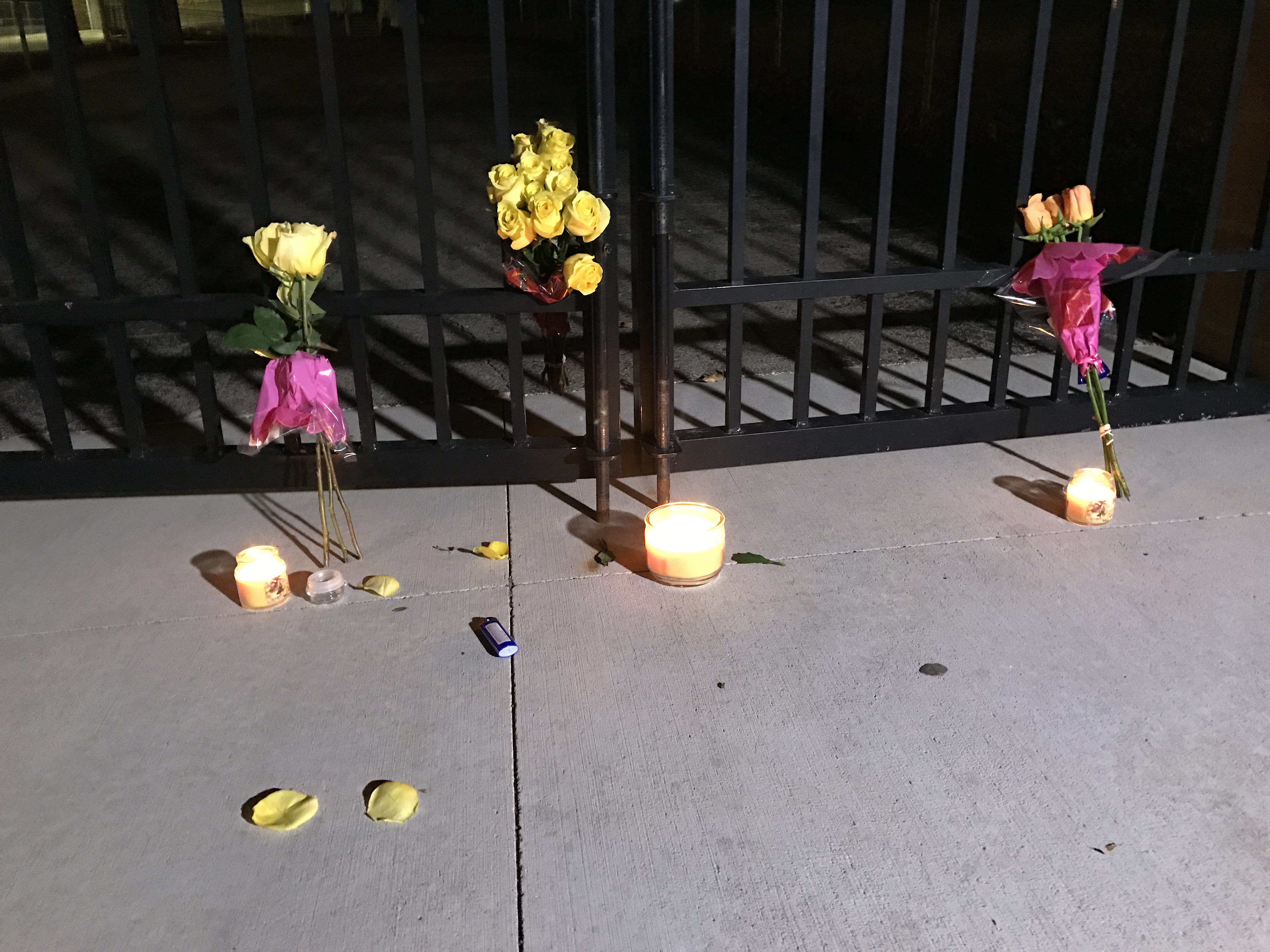Candles and flowers are left outside Blue Valley High School Sunday.