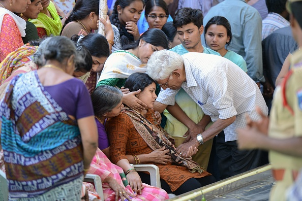 Sunayana Dumala (C), wife of killed Indian engineer Srinivas Kuchibhotla, who was shot dead in the US state of Kansas, is consoled by family members prior to performing the last rites at his funeral in Hyderabad on February 28, 2017. Thousands of Indians visit the United States every year for work or study, and the killing of 32-year-old engineer Srinivas Kuchibhotla in a Kansas bar last week has caused shockwaves around the country. / AFP / NOAH SEELAM (Photo credit should read NOAH SEELAM/AFP/Getty Images)