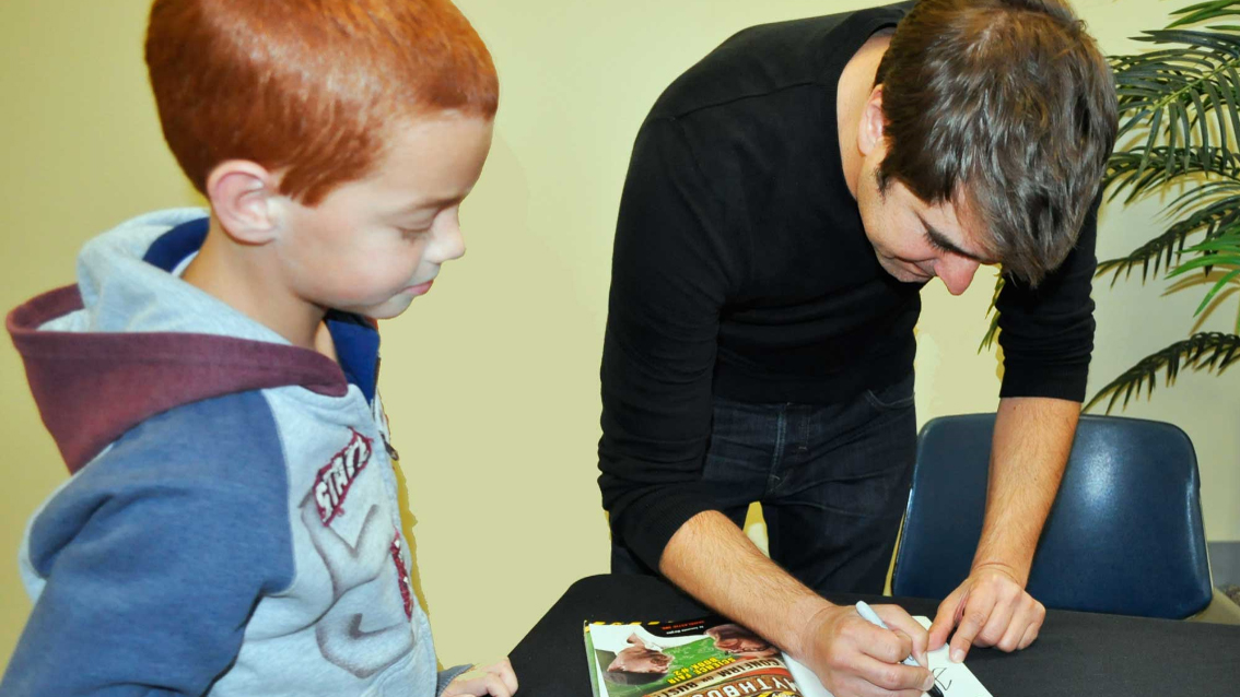 """Henry George, 8, from Thomasville has his copy of the book """"MythBusters – Confirm or Bust"""" signed by Tory Belleci."""