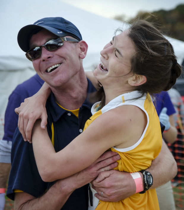 Mount Tabor cross country coach Patrick Cromwell hugs an emotional Kayla Montgomery as she wins the girls NCHSAA 4-A state title at Ivey Redmon Sports Complex in Kernersville on Saturday, Nov. 2, 2013.