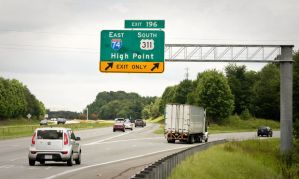 A new sign shows Interstate 74 and US 311 splitting off from Interstate 40 on the southeast side of Winston-Salem, even though that stretch of road doesn't meet federal guidelines to be called an interstate. (Andrew Dye/Journal)