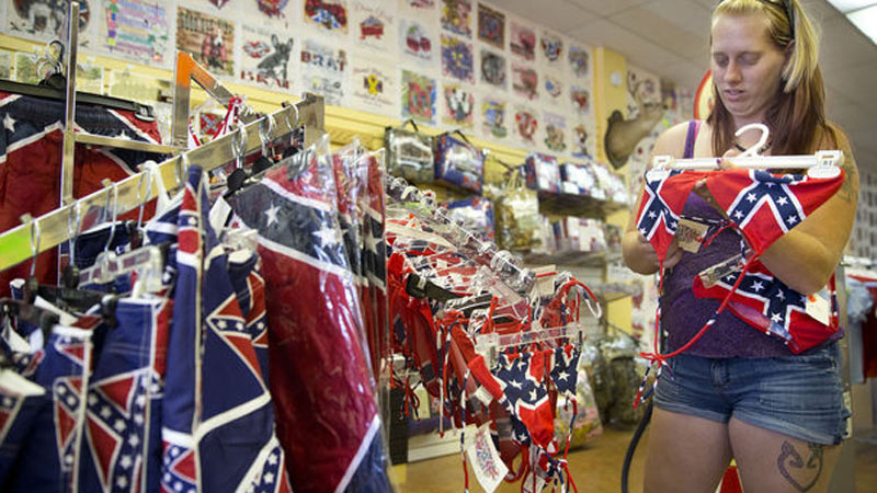 Rebecca Hopkins of Burlington, N.C., looks over a selection of Confederate bikinis at Dixie Outfitters in Burlington, N.C., Friday, July 10, 2015. Hopkins purchased a bikini, a knife, earrings and a miniature Confederate flag Friday at the business. (Greensboro News & Record)