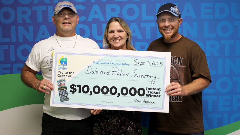 """Dale Summey, left; his wife, Robin; and his son, Dustin, celebrating the win at lottery headquarters with the """"Big Check."""""""