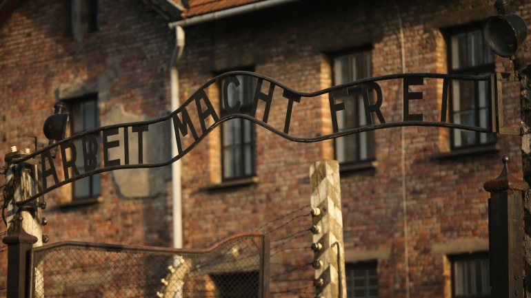 """The infamous German inscription that reads """"Work Makes Free"""" at the main gate of the Auschwitz I extermination camp.(Photo by Christopher Furlong/Getty Images)"""