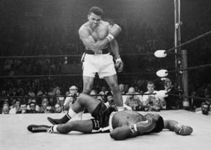 In this May 25, 1965, file photo, heavyweight champion Muhammad Ali, then known as Cassius Clay, stands over challenger Sonny Liston, shouting and gesturing shortly after dropping Liston with a short hard right to the jaw, in Lewiston, Maine. Ali's body will ride in a miles-long procession spanning his life — from his boyhood home where he shadowboxed and dreamed of greatness to the boulevard that bears his name and the museum that stands as a lasting tribute to his boxing triumphs and his humanitarian causes outside the ring. Ali died last Friday at 74 after a long battle with Parkinson's disease. (AP Photo/John Rooney, File)